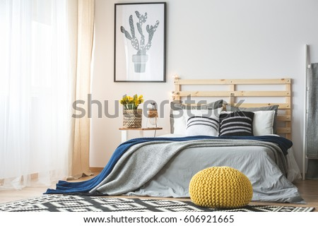 Trendy bedroom interior with king-size bed, pouf, flowers and cactus poster #606921665