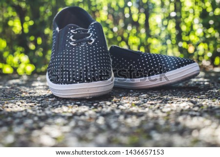 Trendy black sport shoes with small white dots placed on rough cement surface in nature – Woman sneakers placed on the ground with green blurred background #1436657153