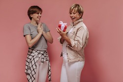 Trendy blonde woman in beige jacket holding small red gift box, smiling and posing with young girl in grey t-shirt on pink backdrop..