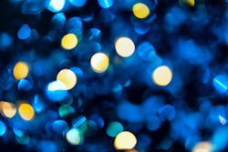 Trendy blue and yellow circles bokeh festive glitter dark background. Christmas lights bokeh overlay pattern. Modern color abstract design.