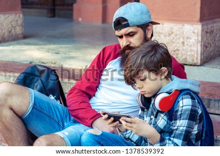 Trendy boy teenage with bearded dad playing a game on the phone. Family relationship father and teenager hipster #1378539392