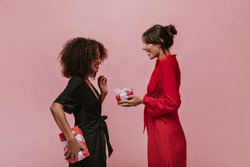 Trendy brunette lady with silver round earrings in red bright dress giving gift her curly friend in dark clothes with box.