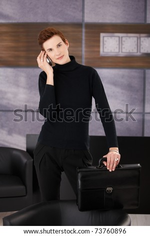 Trendy businesswoman standing in office with briefcase in hand, taking mobile call, smiling at camera.?