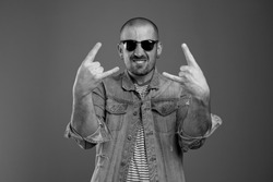 Trendy cheerful man in casual clothes and sunglasses feeling proud of himself while showing rock signs with both hands