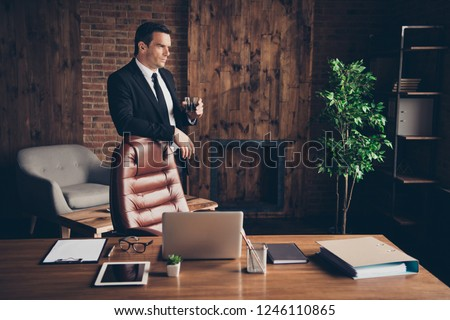Trendy classy elegant attractive handsome minded serious man business shark holding in hand whiskey glass at loft work place station table desktop #1246110865
