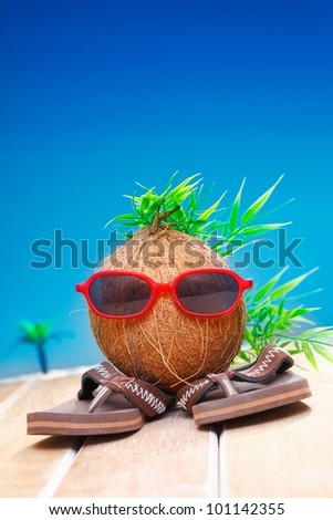 Trendy coconut with foliage hairstyle and natty red sunglasses wearing slip slops as he goes on his travels