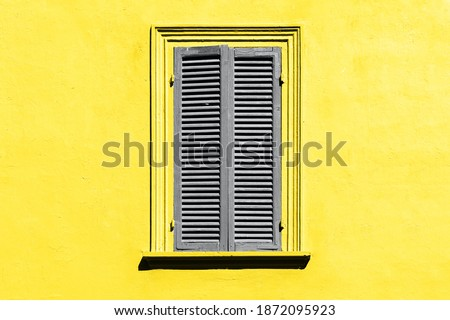 Trendy color of the year 2021. Ultimate grey and illuminating yellow. Gray shutters on the window against a yellow wall. Old window exterior in italian or greek village