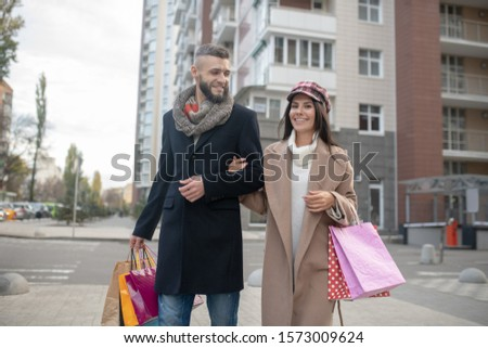 Trendy couple. Pretty happy woman holding her boyfriends hand while shopping together #1573009624