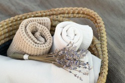 Trendy decor for cozy home. Beautiful items from natural materials. Rolled towel, folded beige cloth, lavender bouquet in a basket. Close up. Nobody. Horizontal. Concept smells, spa, bath decor.