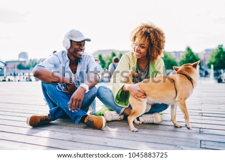 Photo of Trendy dressed african american guy listening music in earphones resting with curly best friend and akita inu, smiling dark skinned romantic couple spending free time outdoors playing with lovely dog