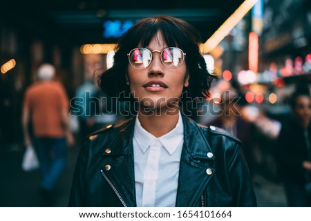 Trendy dressed tourist in stylish eyeglasses with neon reflection looking up during evening sightseeing around metropolitan downtown, fashionable woman in spectacles hanging out in night city