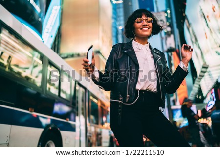 Trendy dressed young woman feeling excited dancing listening favorite music song in earphones, happy hipster girl with modern smartphone having fun on evening city street with neon illumination