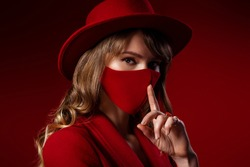 Trendy Fashion accessory during quarantine of  coronavirus pandemic. Woman wearing luxury total red outfit with designer protective face mask. Close up studio portrait. Copy, empty space for text