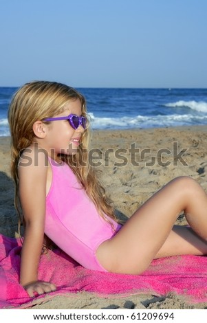 Trendy fashion little summer girl on beach sand tanning with sunglasses