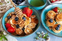 Trendy food during coronavirus Covid-19 lockdown quarantine - tiny pancakes. Poffertjes, Little Dutch pancakes. Breakfast for kids, mini pancakes.