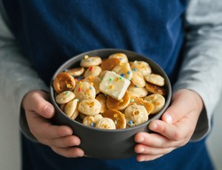 Trendy food - pancake cereal. Heap of mini cereal pancakes in boul in kids hands. Unrecognizable child hold gray bowl with tiny pancakes decorated sprinkles and butter. Copy space for text or design