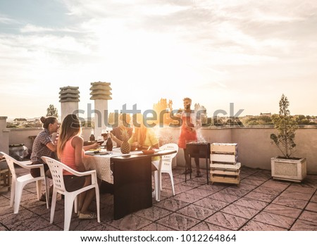 Trendy friends having barbecue party on top of the roof - Happy people doing bbq dinner outdoor - Main focus on woman with yellow t-shirt - Fun, summer, city lifestyle and friendship concept