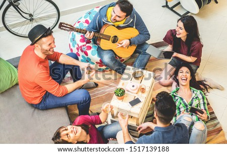 Trendy friends having fun in hostel at party night - Happy travel people enjoying time together playing music - Friendship, nightlife and youth concept - Main focus on right girls faces #1517139188