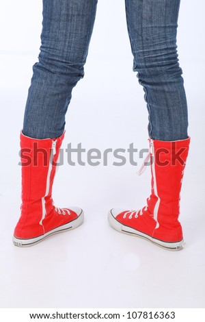 Trendy funky female or male hi top red canvas and white rubber boxing style trainer boots worn with blue jeans and facing backwards with heels showing