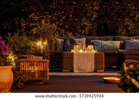 Trendy furniture, lights, lanterns and candles in the garden at night