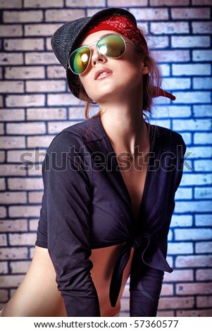 Trendy girl teenager posing  against a brick wall. - stock photo