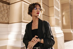Trendy girl with wavy hairstyle and red lips posing outside. Brunette woman in dark jacket and glasses looks away outdoors..