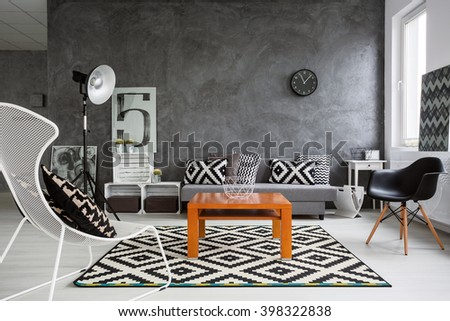Trendy, grey living room with sofa, chairs, standing lamp, wood coffee-table and pattern decorations in black and white  - Shutterstock ID 398322838