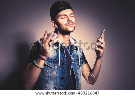 Trendy guy listening to music on his cellphone