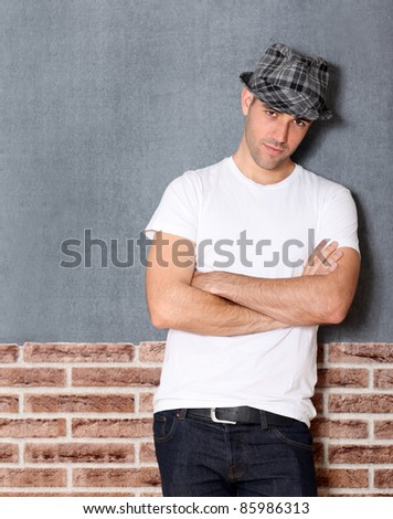 Trendy guy with arms crossed on urban background - stock photo