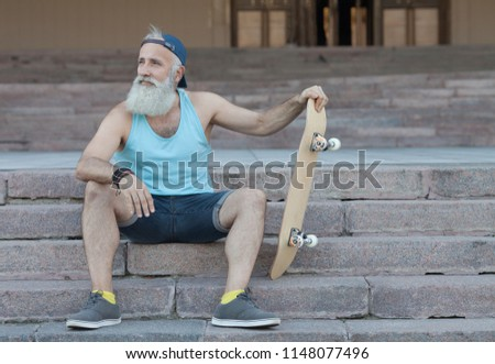 trendy guy with skateboard in town, relaxing on stairs  #1148077496
