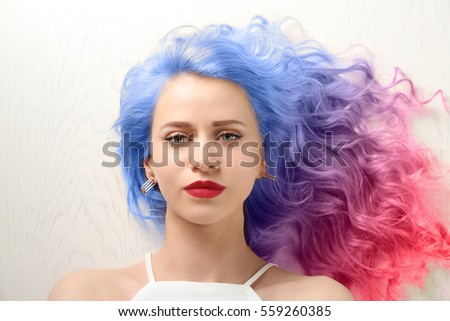 Trendy hairstyle concept. Young woman with colorful dyed hair on white wooden background