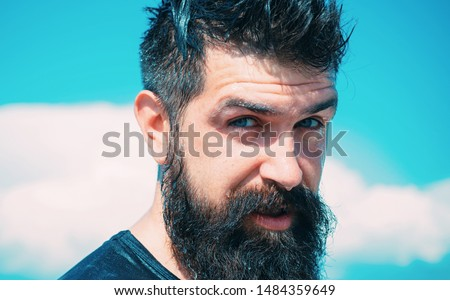 Trendy hairstyle for bearded man. Bearded man on sunny sky background. Brutal caucasian hipster with wet beard and mustache hair on bearded face.