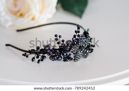 trendy headband with black stones. Girls fashion.Black crown. tiara of artificial stones isolated on white table.joyful hair accessories . Selective focus.Copy space