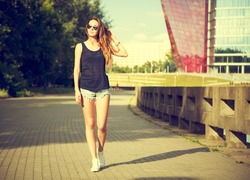 Trendy Hipster Girl Walking in the Park. Toned and Filtered Photo. Modern Youth Lifestyle Concept.