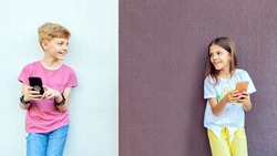 Trendy hipster kids using mobile phones while keeping social distance – Modern children having fun outdoor watching video on smartphones – Digitally happy Gen z boy and girl sharing content online