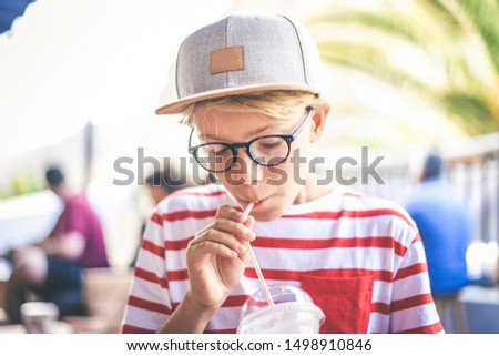 Trendy kid drinking a milkshake at the bar. Colorful portrait of young boy holding a glass with a fresh beverage. Teen sucks a cold drink with a straw enjoying taste. Greedy, gluttonous tasty concept.