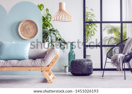 Trendy living room interior with white and blue wall and comfortable couch #1451026193