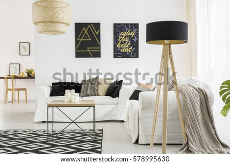 Trendy living room with white sofa, black lamp and table