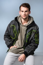 trendy man in hoodie and parka posing while sitting on white cube isolated on grey