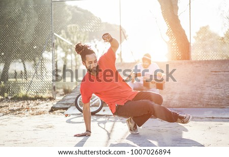 Trendy man making video feed of his breakdancer friend dancing in city park outdoor - Young people having fun sharing media online - Focus on dancer face - Youth lifestyle and friendship concept ストックフォト ©