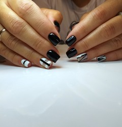 trendy manicure design in the style of minimalism. In manicure, trendy stylish geometric shapes, haze marble technique. Black, whate , gel polish
