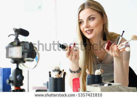 Trendy millenial beauty woman blogger stylist hold in hand cosmetic equipment. Online web broadcast internet on home background concept