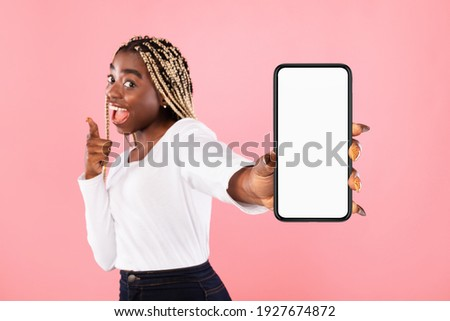 Trendy Mobile Phone. Excited young black lady holding smartphone with white empty screen in hand, showing device close to camera. Gadget with blank space, mockup, selective focus, blurred background
