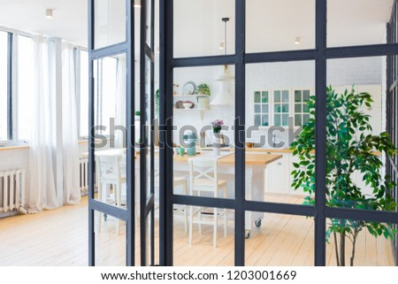 trendy modern design two-level  apartment with large high windows. The stylish living room and kitchen in bright colors are undressed by a glass partition. bedroom on the second floor. #1203001669