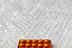 Trendy modern minimalistic background of orange pills blister. Bubble bag background. Packages of tablets in blisters are arranged horizontally. Frame for design. Selective focus.