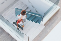 Trendy mother and son walking on stairs in a modern city context. Young boy with skateboard goes up the ladder with mum. Top view of people walks in a modern mall. Family scene at the shopping center