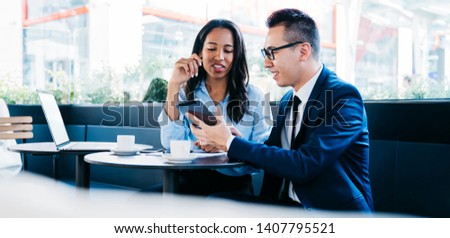 Trendy multiracial woman and man in glasses sharing tablet while having business meeting in cafe sitting at table with cups of coffee