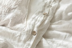 Trendy organic natural linen bedclothes with wooden buttons closeup. Bedding, morning light, bedroom style and design. Rough textile background with wrinkle.