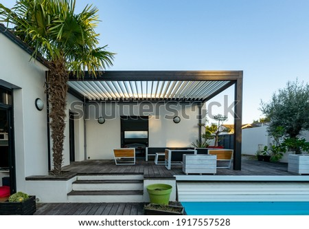 Trendy outdoor patio pergola shade structure, awning and patio roof, garden lounge, chairs, metal grill surrounded by landscaping