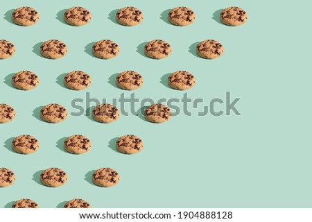 Trendy pattern made  of chocolate chip cookies on bright green mint background. Minimal concept, diagonal copy space.